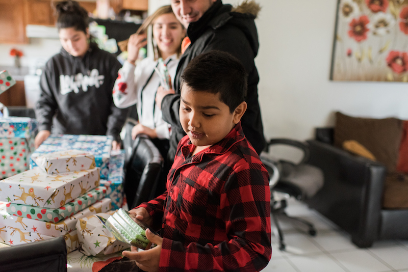 hope for the holidays child opens gifts