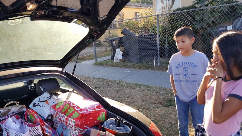 hope for the holidays mentees look at a car full of gifts