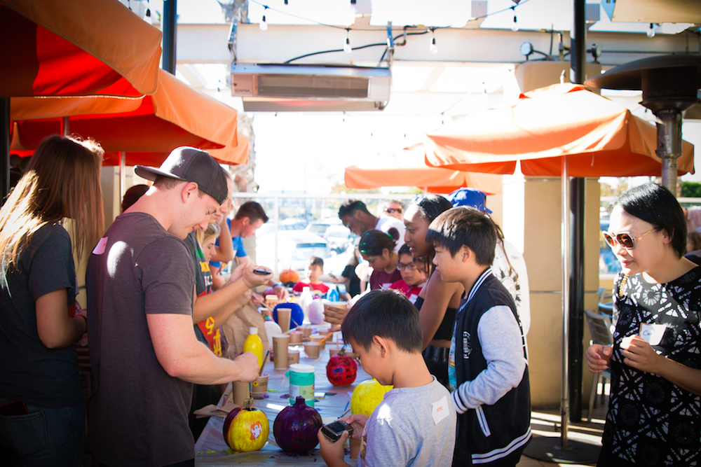 Mentors and Mentees painting pumpkins at California Pizza Kitchen's bonus activity