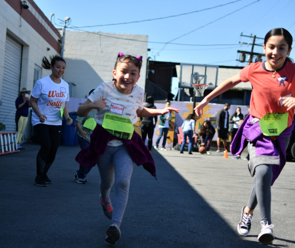 Two mentees participate in the relay race for Walk With Sally's Friendship Activity at Mychal's Learning Place in Hawthorne, Los Angeles, California