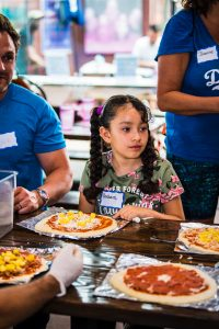 Mentee Barbie making pizza at the Walk With Sally Friendship Activity in Los Angeles